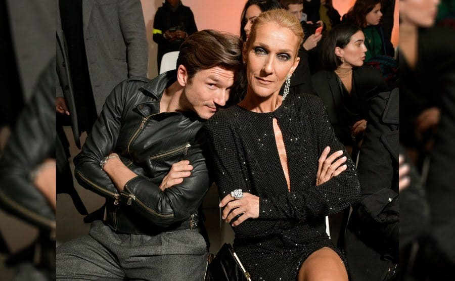 Pepe Munoz is leaning his head on Celine Dion's shoulder in the front row of a fashion show.