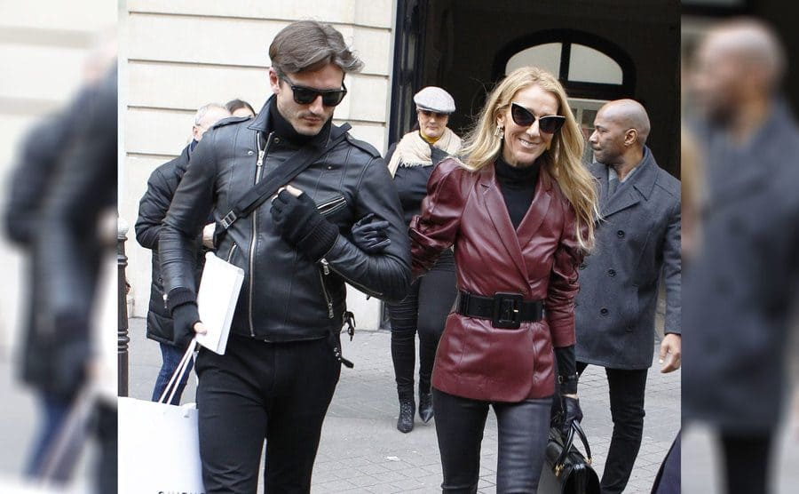 Celine Dion was walking and holding Pepe Munoz's arm.