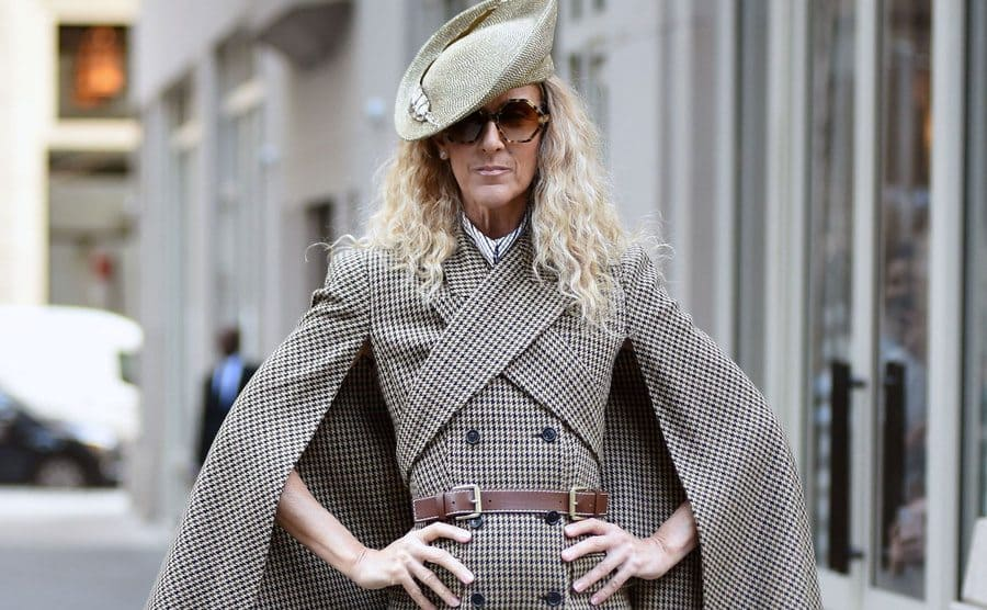 Celine Dion out and about in New York wearing a printed suit with a cape and matching hat.