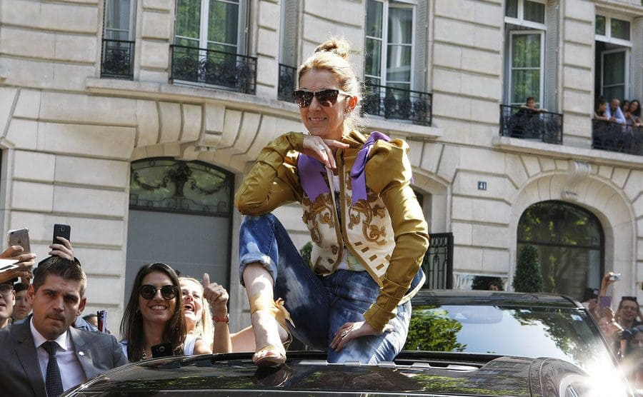 Celine Dion was sitting on the edge of a car's sunroof with jeans, heels, and an embroidered gold and purple jacket on.