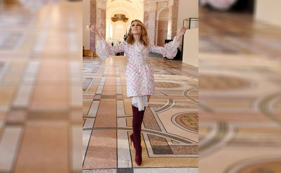 Celine Dion with her arms up.