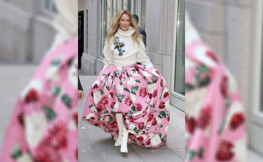 Celine Dion out and about wearing Oscar De La Renta, a cream sweater with embroidered flowers and a puffy over-the-knee floral pink skirt with high white boots.
