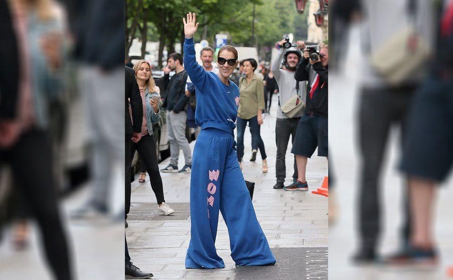 Celine Dion was wearing a blue sweatshirt with matching wide-leg sweatpants waving.