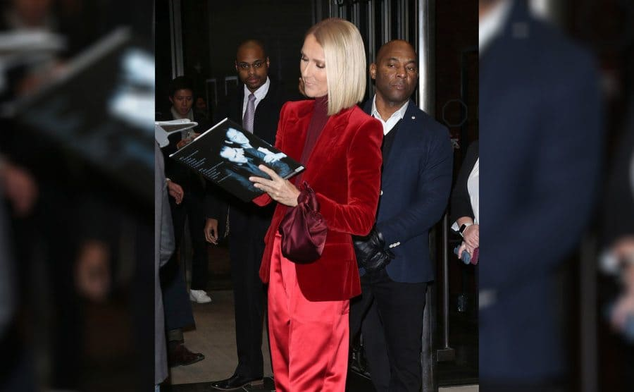 Celine Dion was signing an autograph while out and about wearing a red suit jacket with a turtleneck and baggy red pants in November 2019.