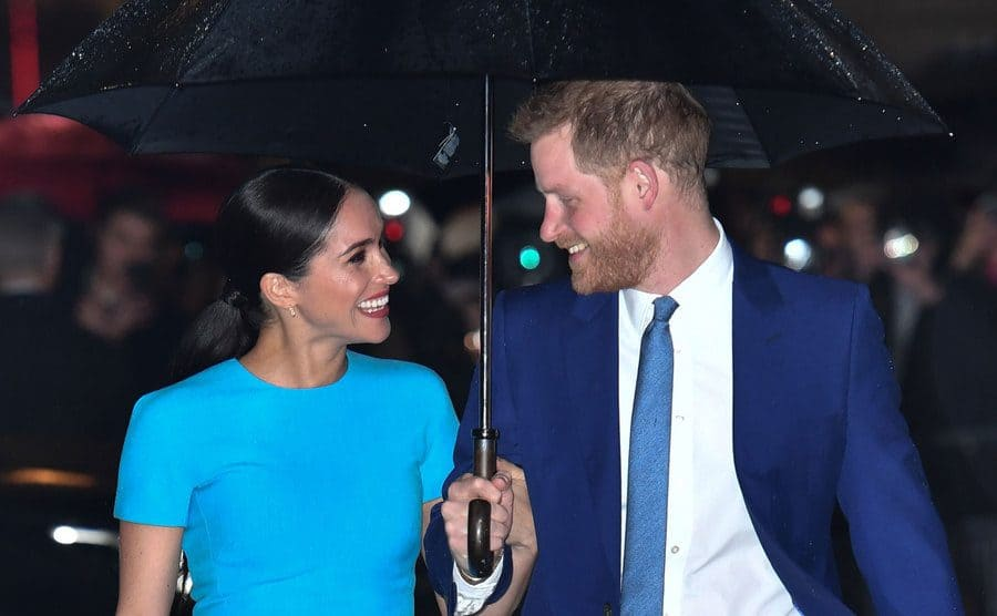 Meghan Markle and Prince Harry sharing an umbrella at the 4th Endeavour Fund Awards in March 2020.