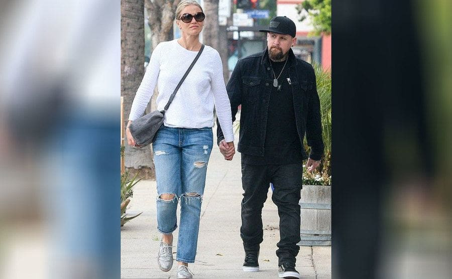 Benji Madden and Cameron Diaz holding hands walking down the street.