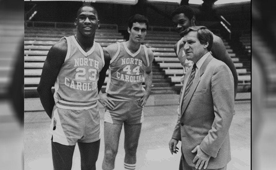 Michael Jordan, Matt Doherty, Sam Perkins, and Coach Dean Smith are posing on the court on October 14th, 1982