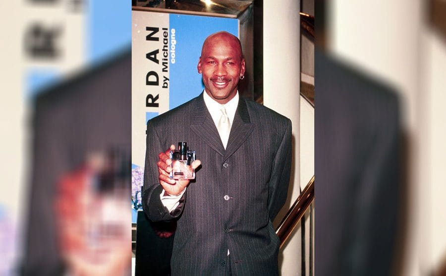 Michael Jordan holding a bottle of his cologne called 'Jordan by Michael'