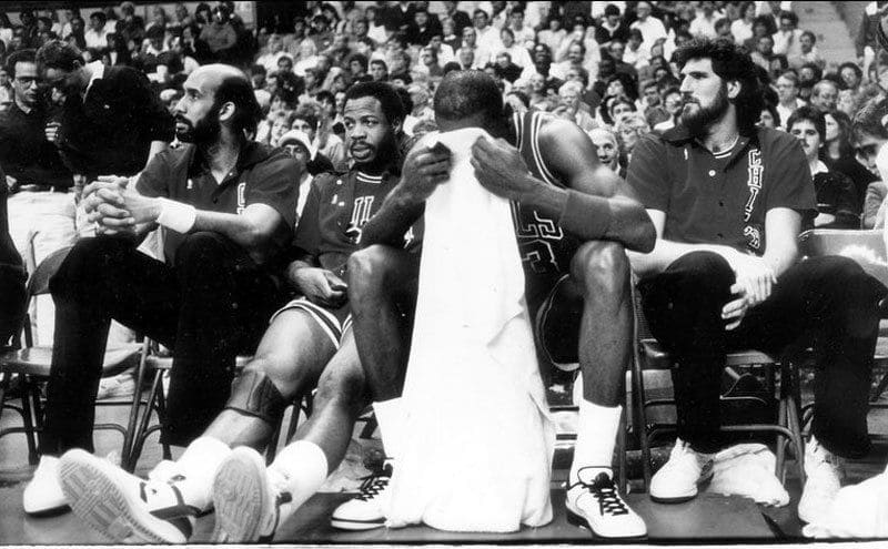 Michael Jordan wipes his brow while he sits between his teammates in a 1987 game