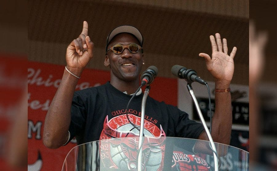 Michael Jordan holding up six fingers, one for each championship, while addressing the crowd at Grant Park in 1998
