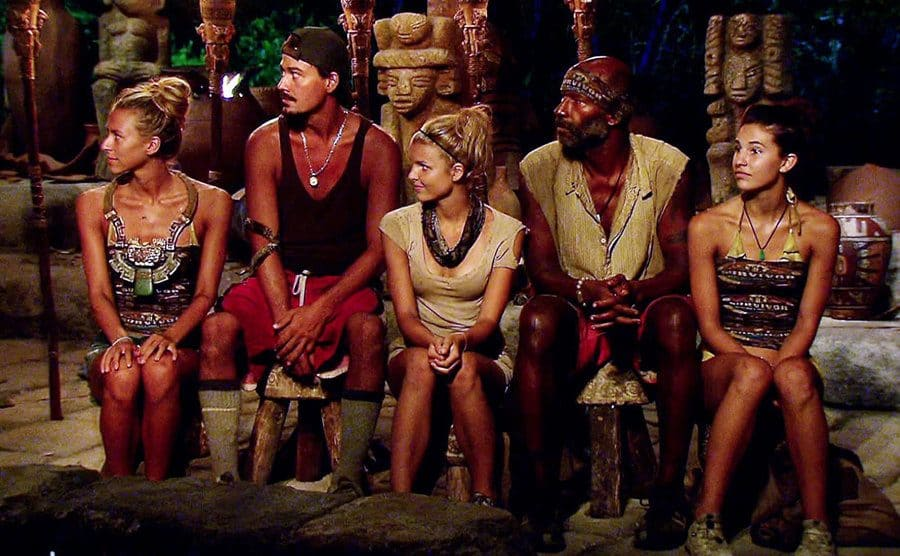 Five contestants on Survivor sitting on a wooden bench with wooden poles and statues decoratively in the background