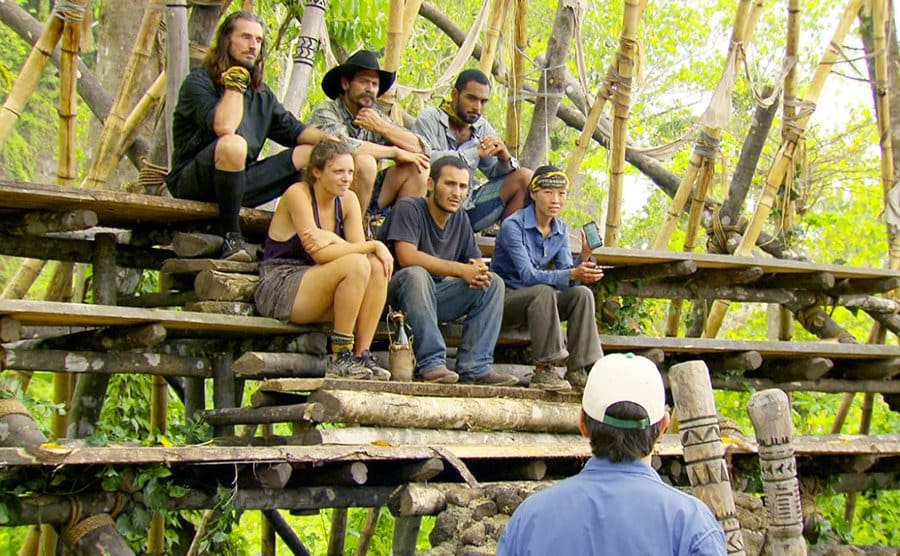 Albert Destrade, Edna Ma, and Brandon Hants with three others sitting in the wooden stands with Jeff Probst addressing them from below