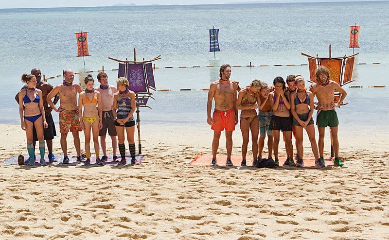 Contestants of Survivor split into two teams in front of a challenge in the ocean