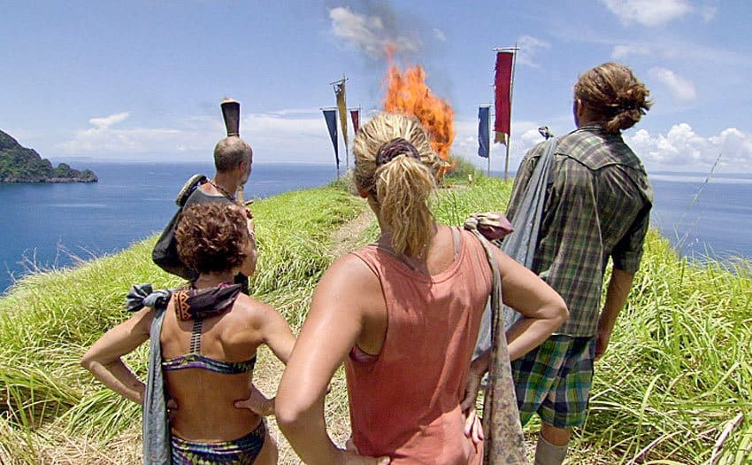 Four contestants looking out at a fire in the grass surrounded by flags overlooking the ocean