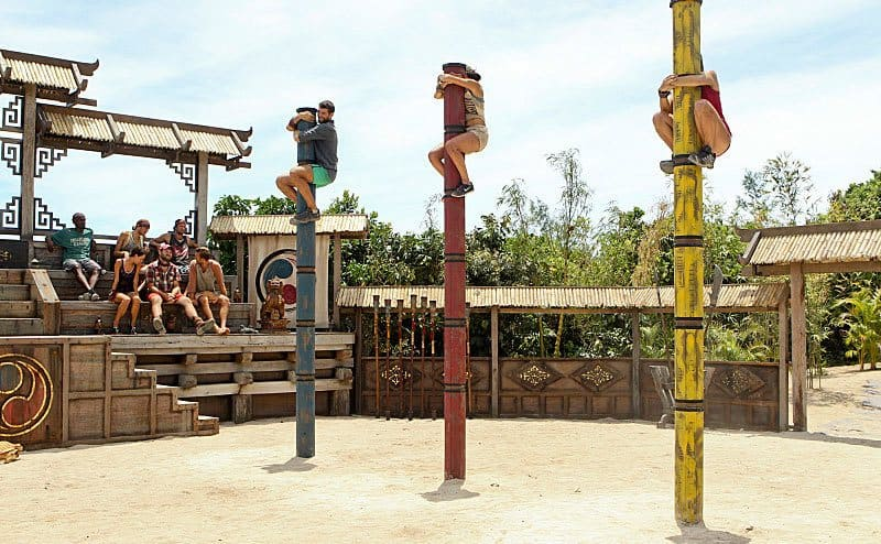 A challenge taking place with Laura Boneham, Laura Morett, and John Cody climbing up very tall poles in red, blue, and yellow