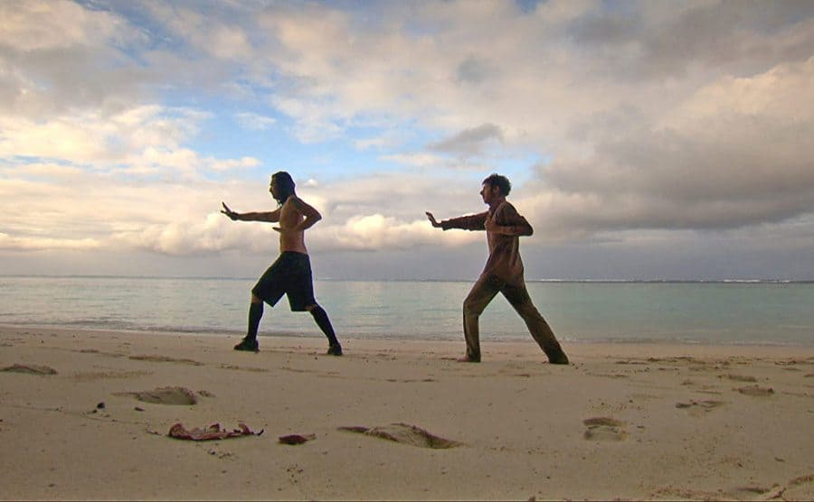 Two contestants exercising together on the beach in Survivor
