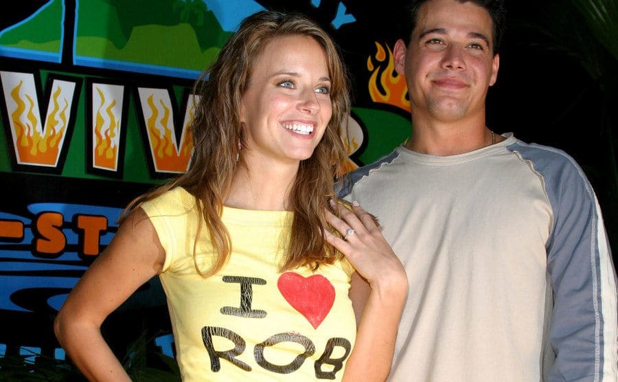 Amber Brkich, wearing an I heart Rob t-shirt and holding up her hand to show off her engagement ring, and Rob Mariano at the Survivor All-Star Finale in 2004