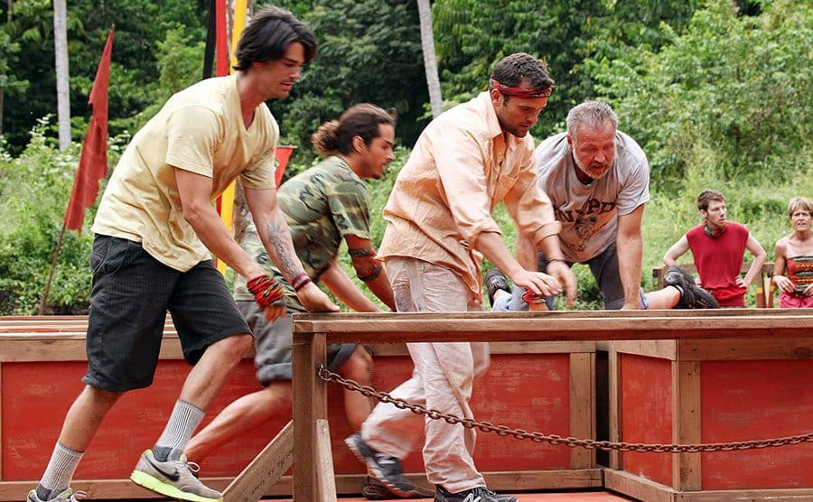 Four guys of different ages competing in Survivor