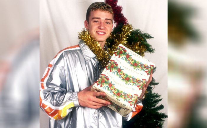 Justin Timberlake holding up a Christmas gift next to a Christmas tree