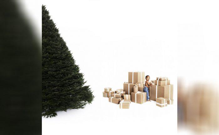 Photo of Saint Kardashian-West with boxes next to an evergreen tree