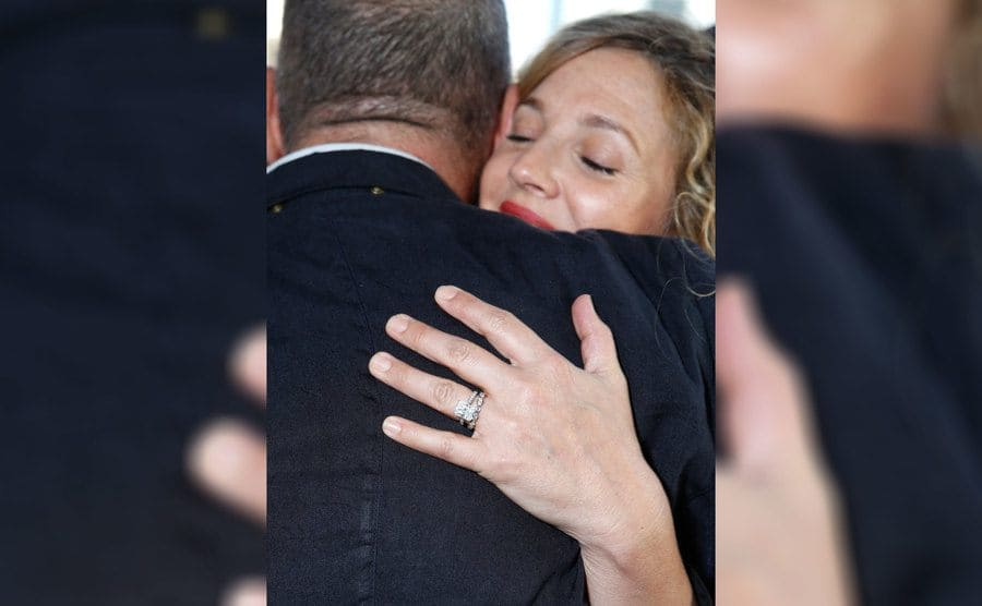 Drew Barrymore's ring detail showing while she hugs a friend