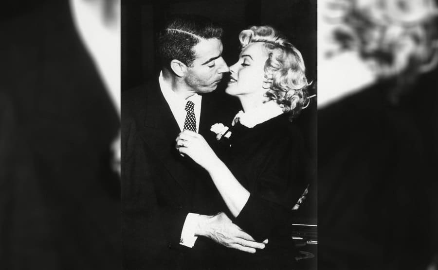 Marilyn Monroe prepares to kiss Joe DiMaggio
