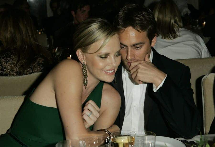 Charlize Theron (L) and Stuart Townsend attend Gucci's charity runway show at the Chow residence.