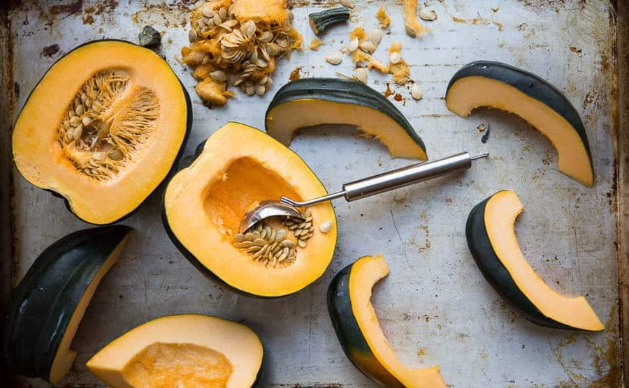 An ice cream scoop is used to remove pumpkin seeds