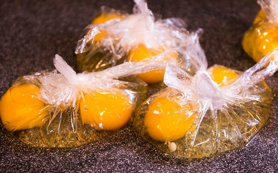 Eggs being poached in plastic bags