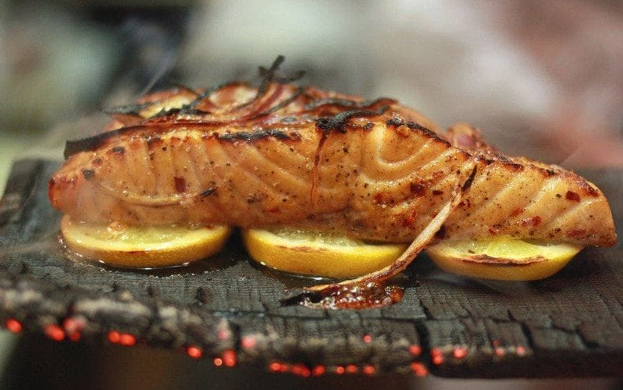 A piece of salmon is grilled on a bed of lemon slices