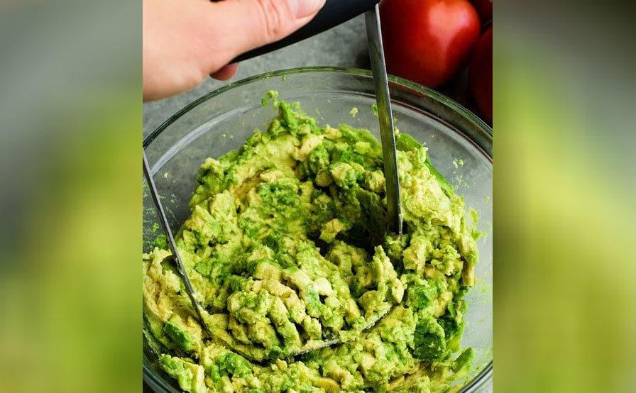 Mashing avocados with a potato masher