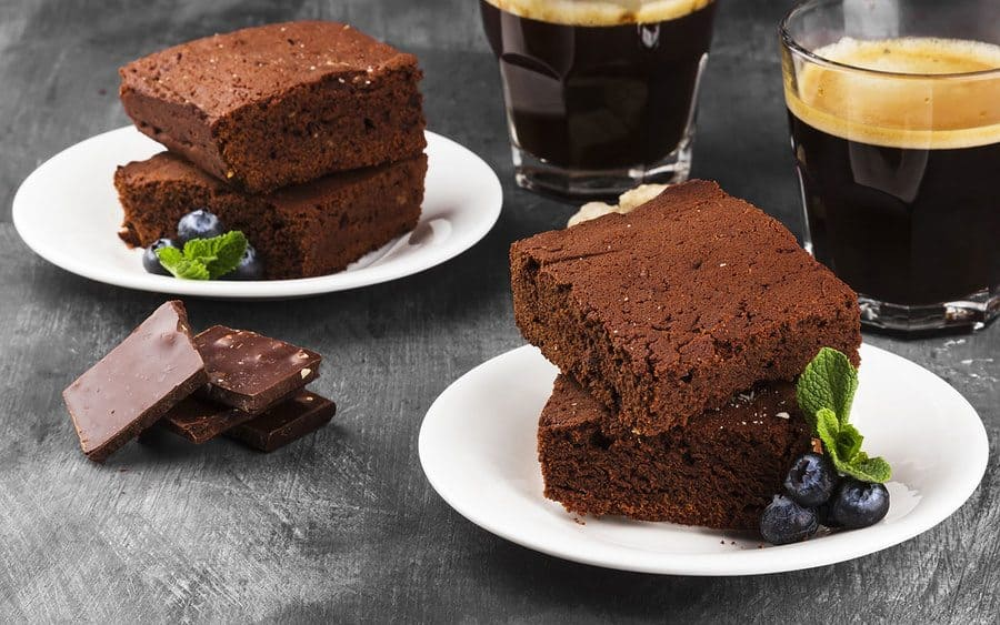Soft brownies made with coffee and two cups of coffee sitting next to them