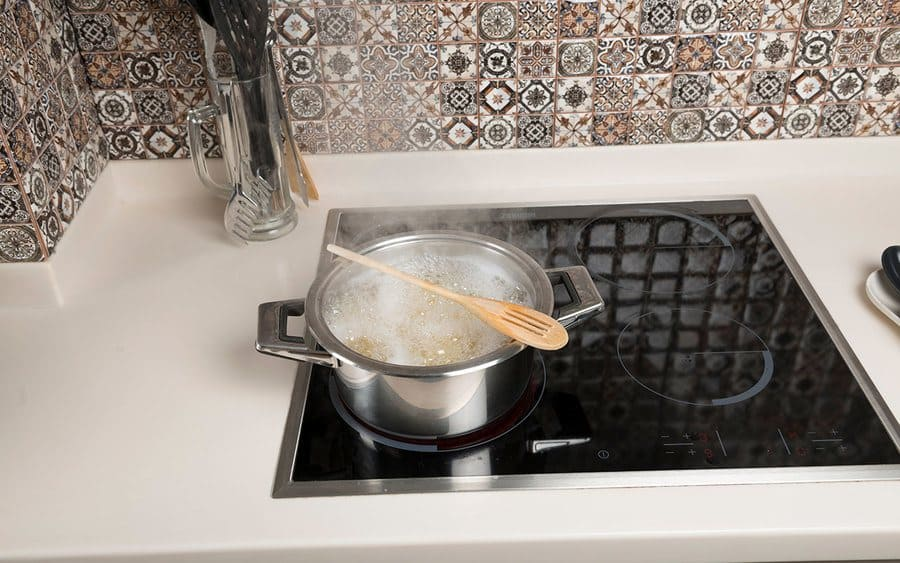 A wooden spoon positioned over a pot with boiling water