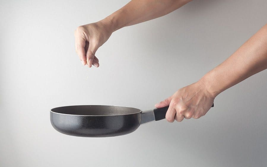 A chef putting some salt into a pan with oil