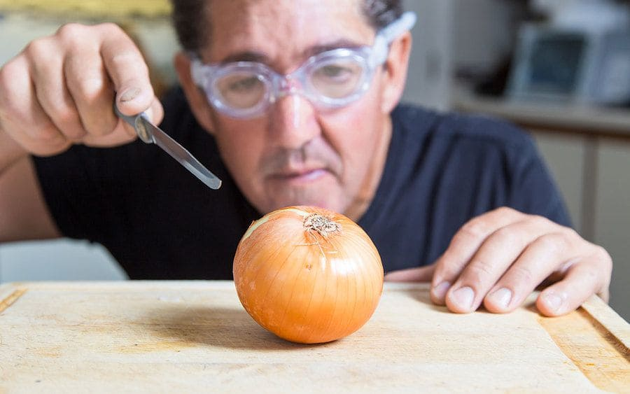A man about to cut an onion with goggles on