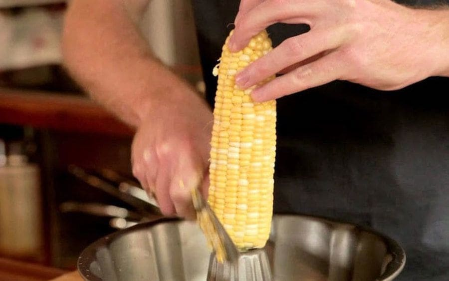A knife and bundt pan are used to de-kernel corn