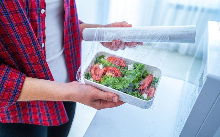 Plastic wrap is used to cover a plate of food