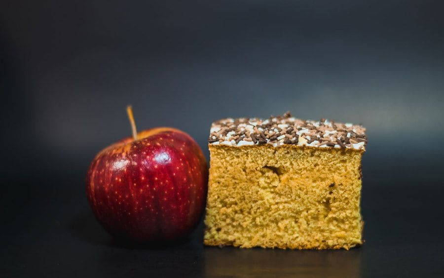 An apple sitting next to a slice of cake