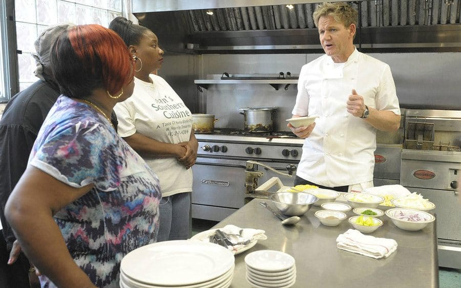 Gordon Ramsay explaining a dish in the kitchen to restaurant owners