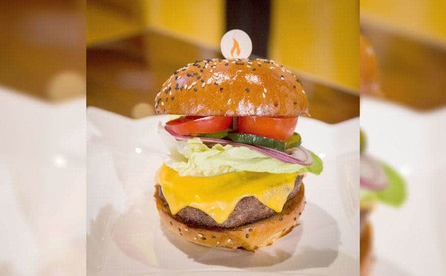 Gordon Ramsay's hamburger with fresh vegetables and cheese melted on it