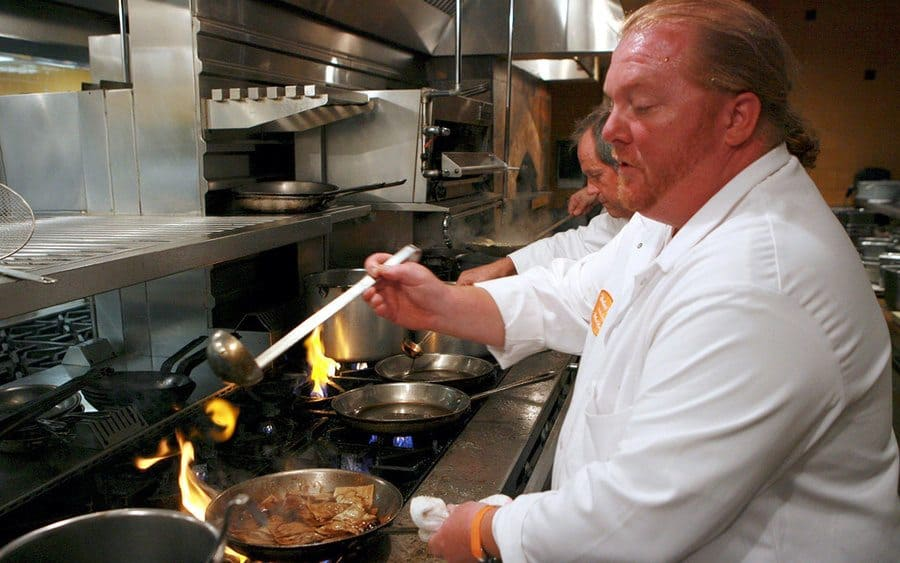 Mario Batali cooking meat on the stovetop