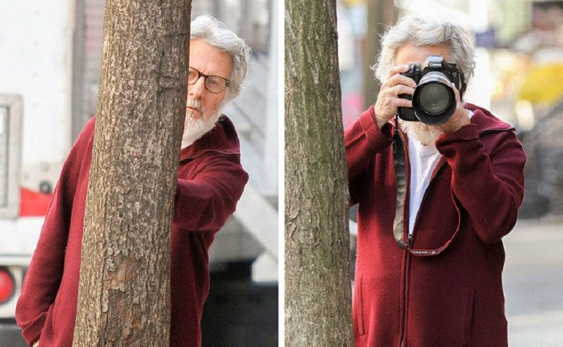 Dustin Hoffman standing behind a tree. / Dustin Hoffman peeking out from behind a tree with a camera to photograph the photographers.