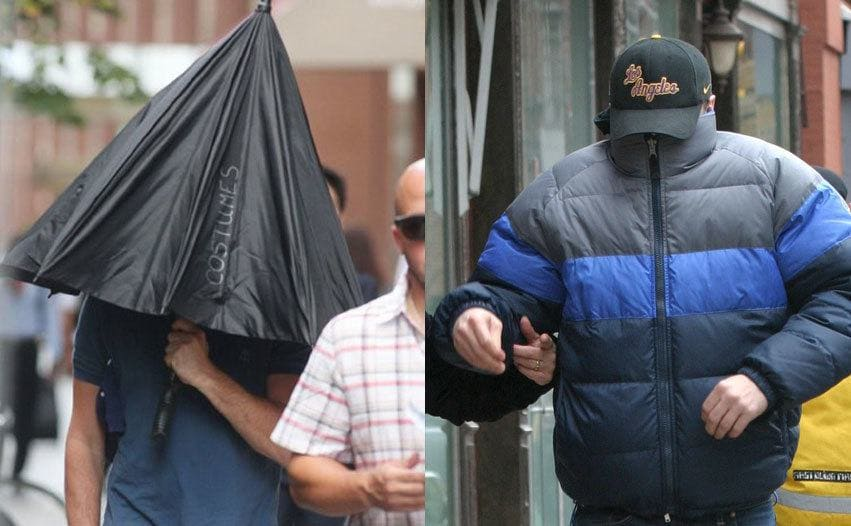 Leonardo DiCaprio hiding underneath a partially opened umbrella which covers his shoulders. / Leonardo DiCaprio with a large puffy winter coat covering his face completely and a baseball cap covering the rest of his head.