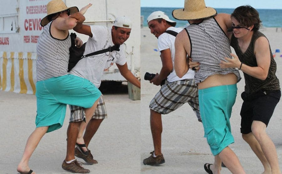 Adam Lambert pushing the paparazzi away while he is at the beach. / A friend intervenes and pulls Lambert away from the paparazzi.