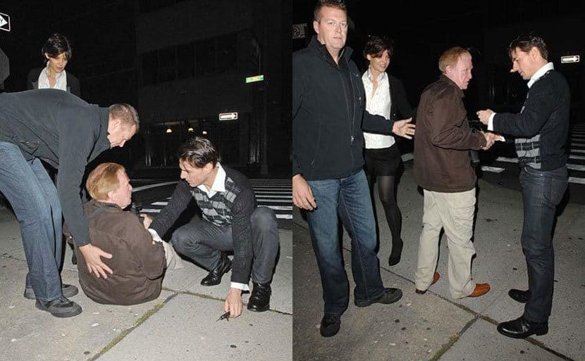 Tom Cruise bending down next to an elderly photographer who had fallen, to help him up again. / Tom Cruise and the photographer shaking hands after Cruise helped him up.