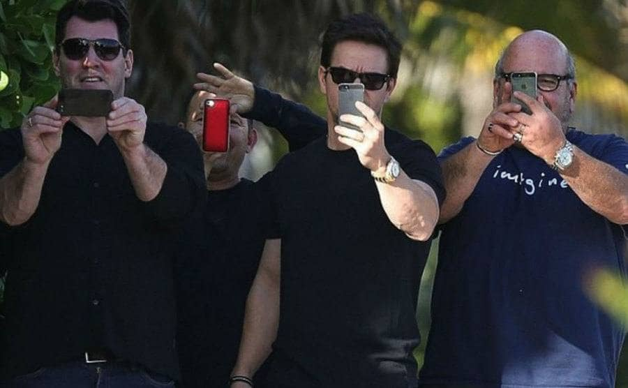 """Mark Wahlberg and his friends with their phones out taking photographs of the paparazzi in a """"photo war."""""""