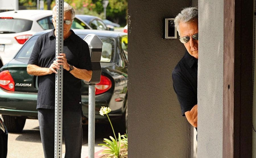Dustin Hoffman hiding behind a pole. / Dustin Hoffman peeking out from behind a wall.