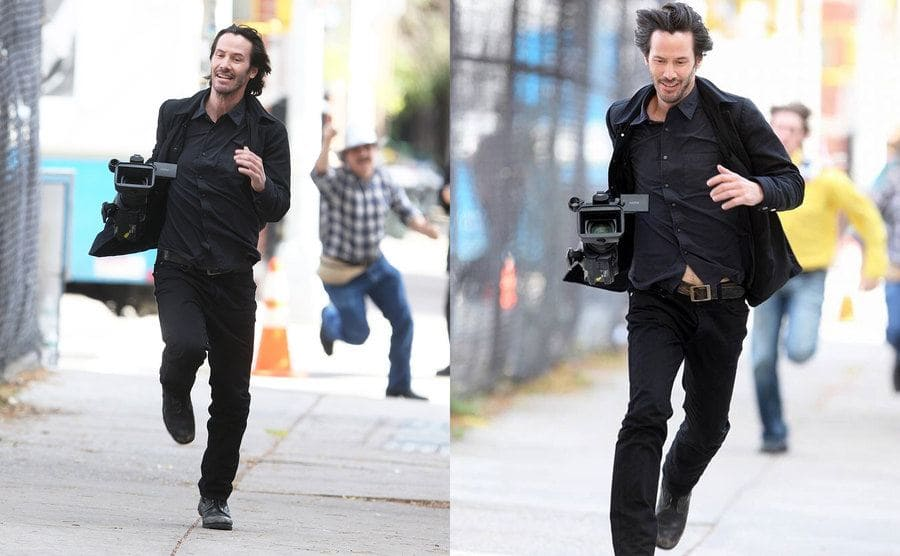 Keanu Reeves stealing a camera and running away from paparazzi. / Keanu Reeves continues to run down the street with the camera with paparazzi running after him.