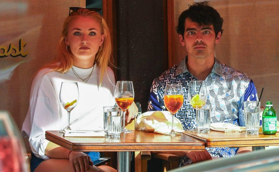 Joe Jonas and Sophie Turner out on a date saying completely motionless while staring forward in hopes that the paparazzi will stop photographing them.