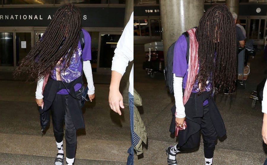 Willow Smith using her long hair to flow around her face to avoid paparazzi. / Willow Smith with her hair dangling down in her face.